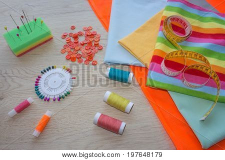 Sewing still life: colorful cloth. Sewing kit includes threads of different colors thimble and other sewing accessories on wooden table