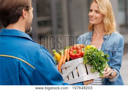 From the store nearby. Charismatic positive young lady meeting the delivery guy outdoors while picking up the box with vegetables he fetching fir her