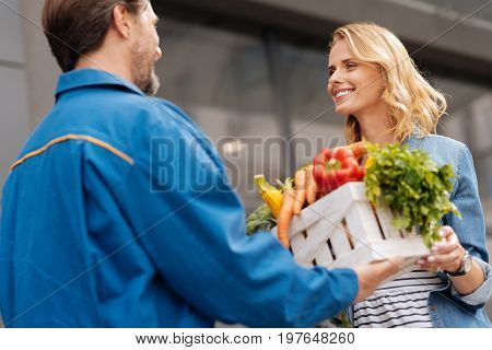 So nice of you. Young charming gorgeous lady thanking pleasant guy for fetching her the vegetables she ordering from the store