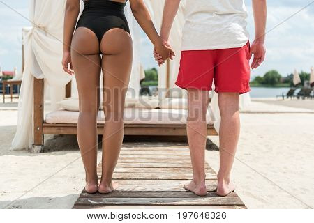 Close up of back of young man and woman standing on wooden beach path hand in hand. They are facing luxury sunbed with soft mattress, pillows and curtains