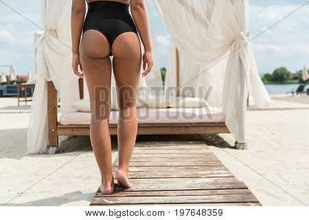 Close up of back of young lady in bikini standing on wooden path to her chic sunbed with soft pillows, mattress and curtains