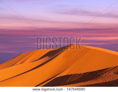 Sand dunes in Sahara desert on sunset sky background
