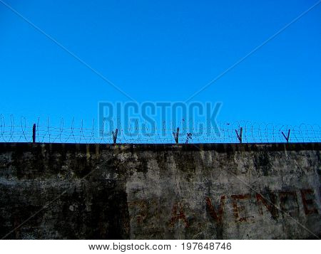 Barbed wire on top of a wall
