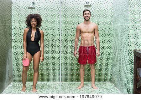 Full length portrait of jolly young african woman and bearded man standing in swimsuits in separate units under dropping water of shower sprayer. They are smiling happily while washing