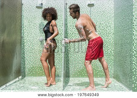 Happy young bearded guy and african lady in swimsuits are washing in shower cubicles. They are covered with soap foam. Man is peeping at girl through separation wall with smile