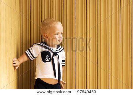 Cute Toddler In A Seaman's Suit Standing Against Wooden Wall. Copy Space.