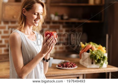 Take care of your nutrition. Healthy pretty admirable lady picking up the best quality ingredients for her meals while cooking at home and being a vegetarian