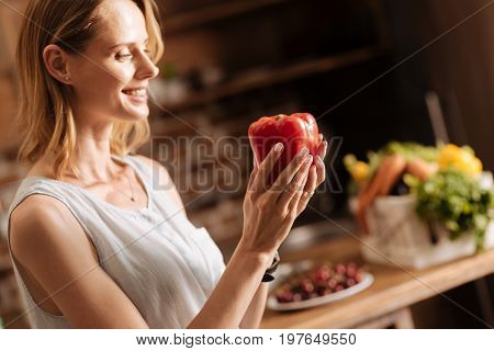 Colorful nutrition. Committed sincere lively lady choosing fresh bell pepper for making a salad at home while being a vegetarian