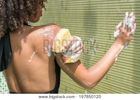 Close up of hands and back of calm young mulatto girl soaping shoulder using bath puff and gel. She is standing by wall and touching it by foamed hand