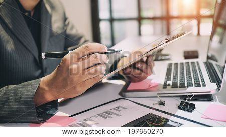 Audit conceptBookkeeper or financial inspector and secretary making report Financial Planning Report in Spreadsheet .Internal revenue Service inspector checking financial document vintage tone.