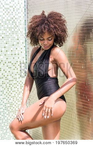 Portrait of cheerful young african girl standing near washing room wall in swimsuit. She is watering her body and looking down with smile