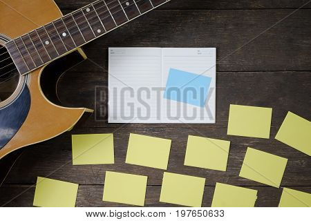 Desk of song composer for a work songwriter with a guitar and notepad on wood table with vintage tone.