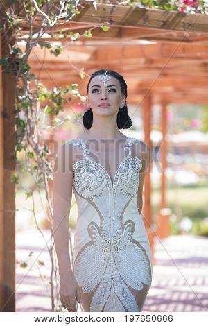 Woman with fashion makeup on young pretty face brunette in white lace wedding elegant vintage dress with jewelry decoration on her forehead posing on wooden blur background outdoor
