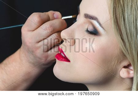 Woman With Closed Eyes And Red Lips Getting Makeup
