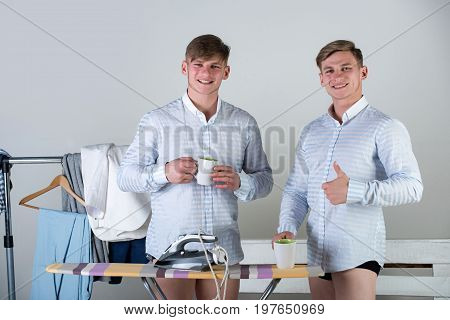 Two Brothers With Happy Smiling Faces On Grey Background