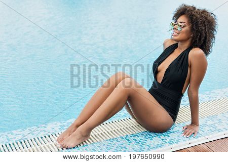 Joyful young mulatto woman is sitting on poolside, keeping bent legs together. She is looking to distance with toothy smile