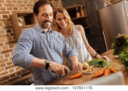 Real gentleman. Witty wonderful positive guy showing off his skills while chopping carrots and making a dinner for two at home