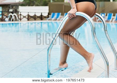 Close up of legs of young woman going down stairs into swimming pool. She is holding metal hand-rail while dipping into blue water