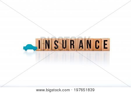 Car Insurance - Wooden Block Letters On White Reflective Background With Blue Car Shape