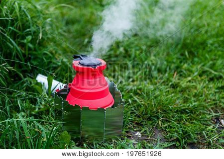 Tourist equipment concept. Fodable camping kettle with boiling water standing on burning stove.