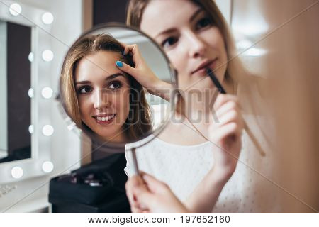 Young female client looking in the mirror while makeup artist working on her eyebrows in beauty salon.