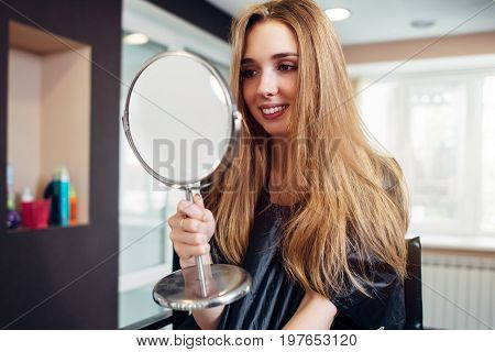 Portrait of happy young woman looking in the mirror sitting in a beauty salon.