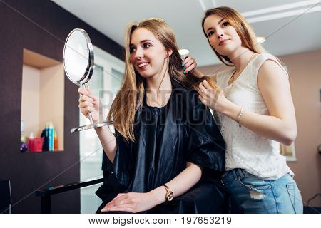 Young female stylist discussing and choosing a new look for a customer sitting on chair looking in makeup mirror in beauty salon. poster