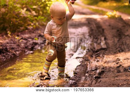Funny Baby Boy In A Rubber Boots Having Fun In A Forest Puddle