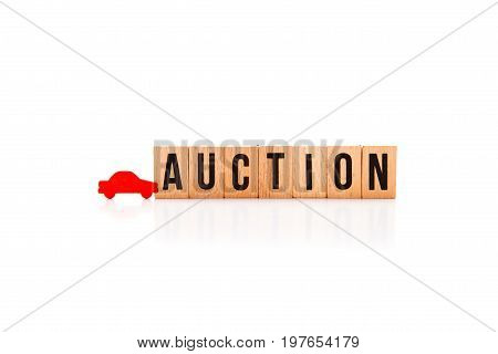 Car Auction - Wooden Block Letters On White Reflective Background With Red Car Shape