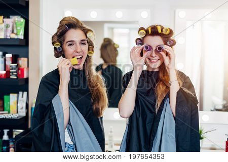 Two funny young girlfriends in hair curlers wearing capes having fun time together in beauty salon. Female friends fooling around with rollers, making faces.