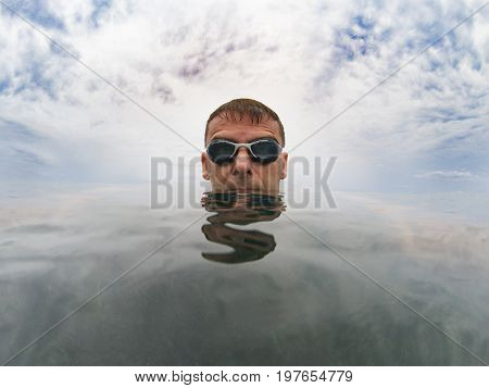 Young serious man in the sea his head is on the smooth surface of the water over him the cloudy sky he wears goggles
