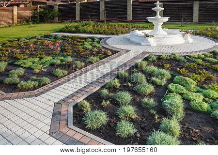 Yard with a fountain and fresh planted plants drip irrigation stone paths wooden fence