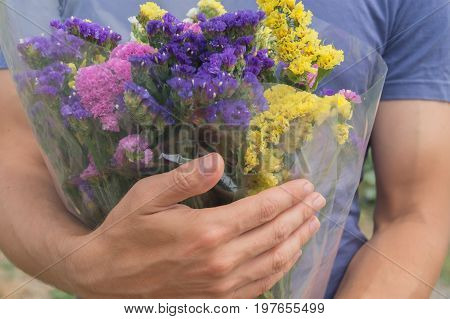 Bouquet of violet yellow pink and white statis in the man's hands