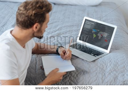 Be attentive. Competent worker looking at screen of computer and making notes while sitting in semi position