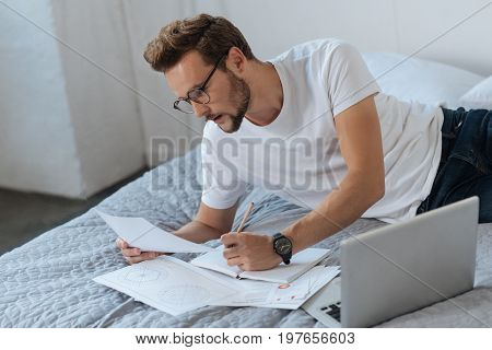 Attentiveness in task. Delighted young man leaning on the bed and bowing head while looking downwards