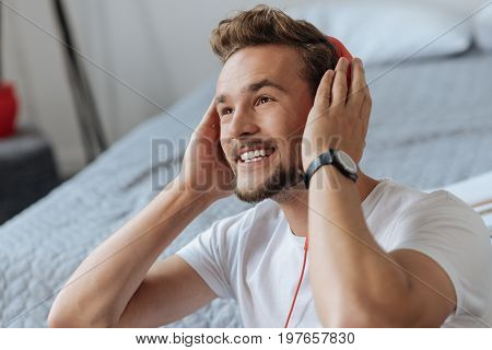 Love my life. Attractive bearded male person raising eyebrows and putting hands on the headphones while looking upwards