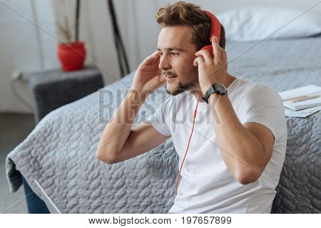 Enjoying music. Positive brunette keeping smile on his face and holding arms bent in elbows while sitting in semi position