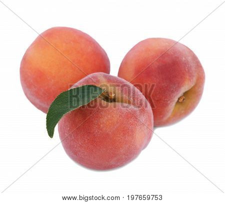 Three whole and juicy peaches with green leaves, close-up. Ripe, appetizing fruit, isolated on a white background. Healthy and organic peaches. Ingredients for nutritious breakfast and summer snack.