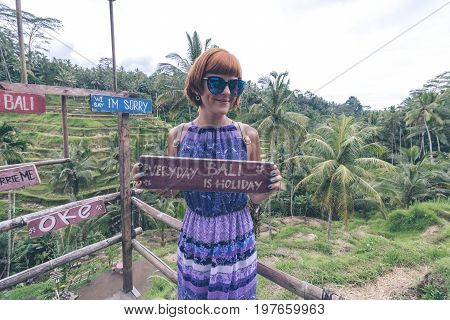 Wooden nameplate with text everyday Bali is holiday in the woman hands on a tropical rice terrace background of Bali island of parardise.