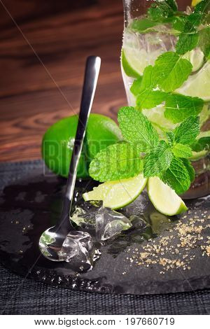 Close-up of a glass of summer mojito beverage from mineral water, juice limes, cruched ice, leaves of mint and brown sugar on a wooden table. Refreshing non-alcohol cocktail with a spoon.