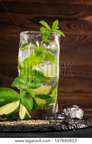 A beautiful green mojito cocktail from mint, limes, rum and cubes of ice on a dark wooden background. An alcohol beverage with fresh lime slices, brown sugar, ice cubes and mint leaves. Alcohol drink.