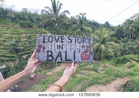 Wooden nameplate with text in the woman hands on a tropical rice terrace background of Bali island of parardise, Indonesia.