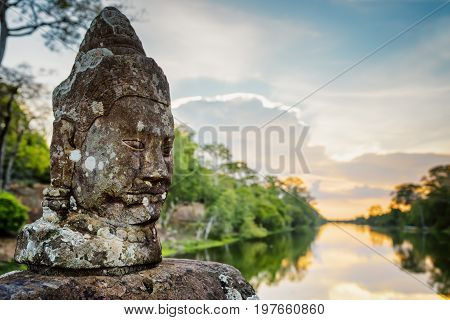 Mossy Stone Face Asura And Sunset Over Moat In Angkor, Cambodia