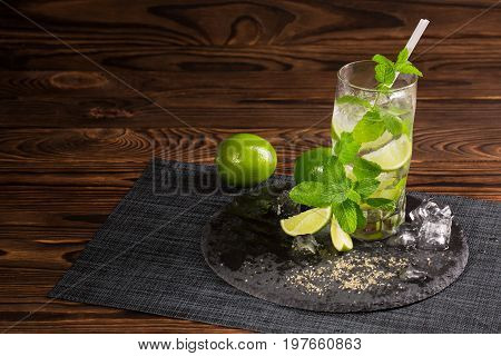 A glass of alcohol mojito on a dark brown wooden background. A cold drink with liquor, rum, mint, limes and cubes of ice on a black plate. Drinks for summer parties. Copy space.