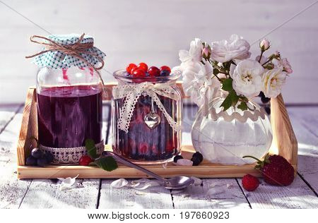 Berry jam in vintage glass jars decorated with ribbons and wild roses. Making fruit jam concept. Fresh berry on wooden table, summer still life and rustic food background. Preserved fruits
