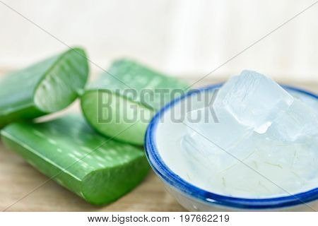 Aloe vera gel on bowl with fresh aloe vera leaves on wooden