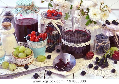 Spoon and vintage glass jars with jam, fresh berry on the table. Making fruit jam concept. Fresh berry on wooden table, summer still life and rustic food vintage background. Preserved fruits