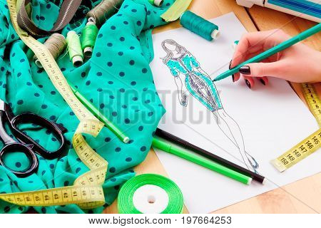 Dressmaker's workplace: scissors ribbons lace pencils sketch fabric measuring tape and band. Girl sketching a dress