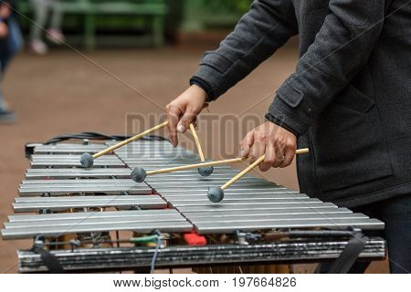 Hands of street musician playing the chromatic glockenspiel (metallophone).