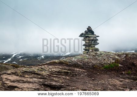 Pyramid of stones in cliff during trip Norway, balancing stone pyramids on a natural background in mountains.